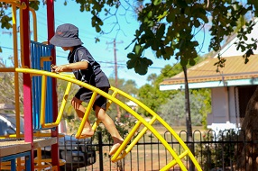 Young boy on arched yellow climbing frame