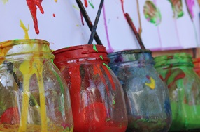 Four primary colour paint jars with spills and paint brushes
