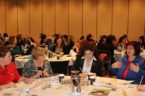 Four female educators sitting around a round table engaging in a discussion at an ACECQA workshop