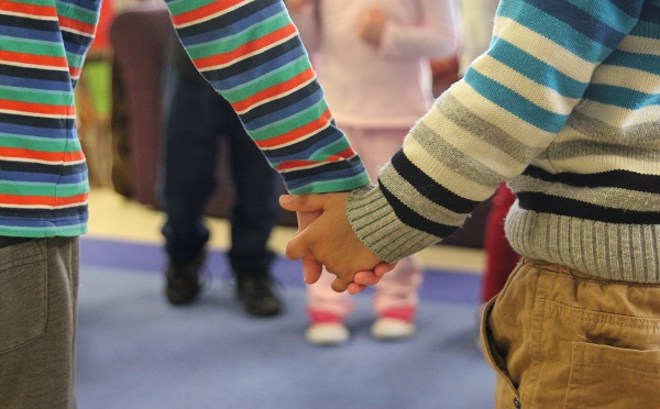 Close-up of two boys in stripey jumpers holding hands