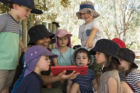A group of young children and a female educator gathered around a tablet device