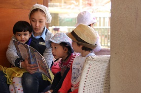 Female educator reading to three young children