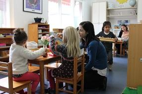 Two little girls crafting at a table while talking to a female educator