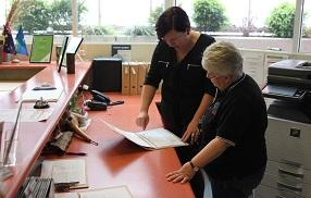 Two female employees reviewing guidelines