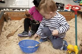 A child playing in a sandpit with a blue bucket