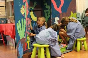 Three school age girls sitting on yellow stools and painting a large mural