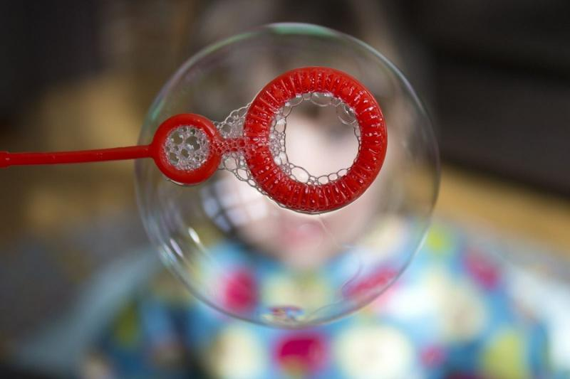 Close-up of soap bubble and red wand.