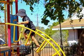 Young boy climbing on a yellow frame