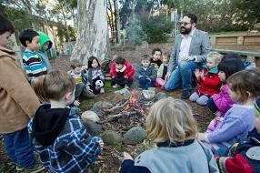 Male Aboriginal educator talking to a group of children sitting around an outdoor fire