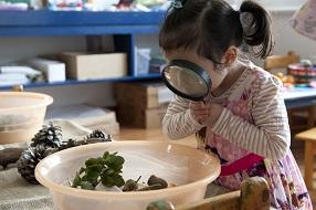 Little girl looking at items in a bowl through a magnifying glass