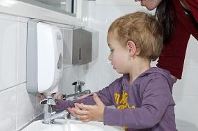 Little boy washing his hands at a bathroom sink