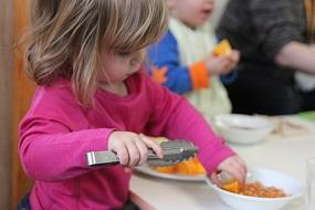 Little girl with tongs getting food
