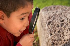 Child looking at rock with magnifying glass