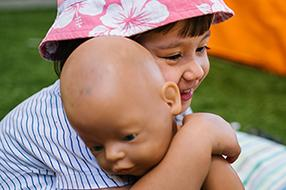 Child wearing hat hugging baby doll