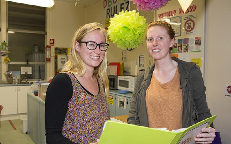 Two smiling educators holding a green folder