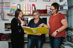 Three female educators looking at a file together